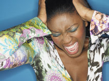 Closeup Of Stressed Young Woman Shouting. Closeup of a stressed young woman shouting against blue background Stock Photography