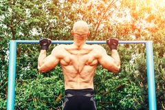 Closeup of strong bald athlete doing pull-up on horizontal bar. back view. Closeup of strong bald athlete doing pull-up on horizontal bar Royalty Free Stock Images