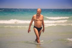 Bearded Old Man Walks out of Sea against White Foamy Waves. Closeup strong tanned bearded old man walks out of azure sea foamy waves against wave surf Royalty Free Stock Images
