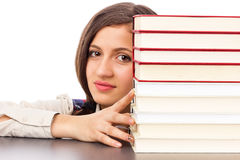 Closeup of student face behind stack of books Royalty Free Stock Photo