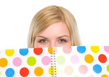 Closeup on student girl hiding behind notebook Stock Images