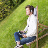 Closeup on student listening to music with closed eyes outdoors. Closeup on a relaxed bearded young man listening to music with closed eyes in french garden with Stock Photography
