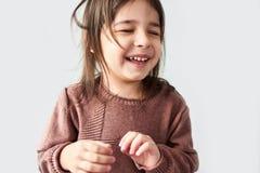 Closeup studio horizontal portrait of happy cute little girl smiling joyful and wearing sweater isolated on a white studio stock photo
