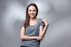 Closeup studio portrait of young woman in grey shirt Stock Image