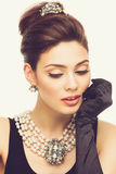 Closeup of stylish girl. Beautiful young woman looking like Audrey Hepburn wearing pearls Stock Image