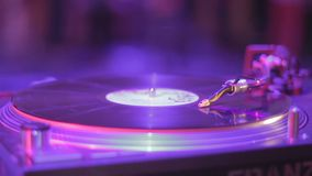 Closeup of stylus, vinyl record rotating, music playing at party. Stock footage stock video footage