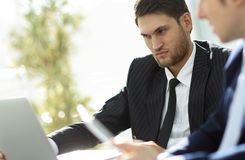 Closeup.successful businessman with a colleague discussing work issues. Sitting behind a Desk.photo with copy space Stock Image