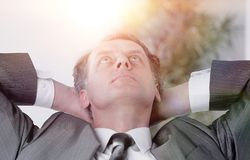 Closeup .a successful businessman relaxarea sitting behind a Desk royalty free stock images