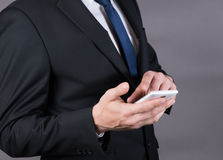 Closeup of a successful businessman using mobile smart phone Royalty Free Stock Images