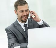 Closeup.successful businessman working on laptop and talking on the phone. Stock Photos