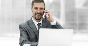 Closeup.successful businessman working on laptop and talking on the phone. Photo with copy space Royalty Free Stock Images