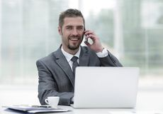 Closeup.successful businessman working on laptop and talking on the phone. Photo with copy space Stock Photos