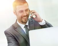 Closeup.successful businessman working on laptop and talking on the phone. Photo with copy space Royalty Free Stock Photos