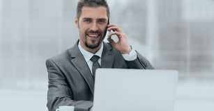 Closeup.successful businessman working on laptop and talking on the phone. Photo with copy space Royalty Free Stock Image