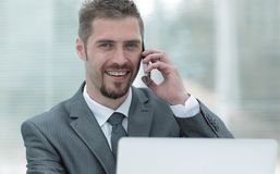 Closeup.successful businessman working on laptop and talking on the phone. Photo with copy space Stock Image