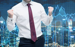 Closeup of successful portfolio manager in white shirt with pumped fists. A concept of the celebrating of success. Forex chart and Stock Image