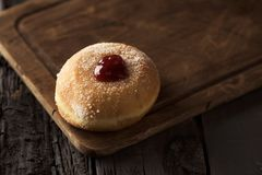 Sufganiyah, Jewish donut eaten on Hanukkah. Closeup of a sufganiyah, a Jewish donut filled with strawberry jelly traditionally eaten on Hanukkah, on a rustic
