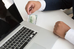 Closeup of an in suit inserting hundred dollar bill in the lapto Stock Image