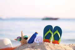 Closeup of Summer beach with accessories of blue flip flops, hat, sun protection cream, towel and sunglasses on starfish in stock photos