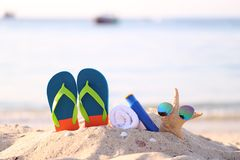 Closeup of Summer beach with accessories of blue flip flops, sun protection cream, towel and sunglasses on starfish in tropical royalty free stock image