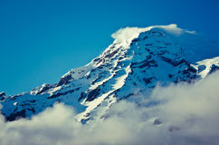 Closeup of summit of a snow capped mountain. While a cloud forms at the summit Stock Photo