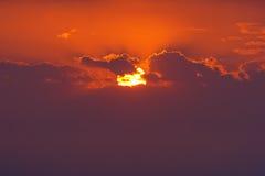 Closeup of sun behind clouds at sunset Stock Image