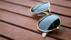 Closeup sunglasses on a wooden table stock video footage