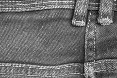 Closeup surface back side of old jean trousers fabric textured background in black and white tone. Closeup surface back side of jean trousers fabric textured Stock Image