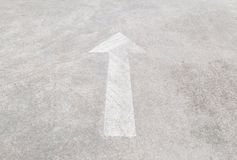 Closeup surface old and pale white painted arrow sign on cement street floor textured background. Closeup old and pale white painted arrow sign on cement street royalty free stock image