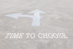 Closeup surface old and pale white painted arrow sign on cement street floor with time to choose word textured background. Closeup old and pale white painted royalty free stock photos