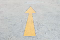 Closeup surface old and pale yellow painted arrow sign on cement street floor textured background. Closeup surface pale yellow painted arrow sign on cement stock photography