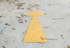 Closeup surface old and pale yellow painted arrow sign on dirty cement street floor by dried leaves textured background. Closeup old and pale yellow painted Royalty Free Stock Photography