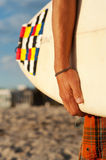 Closeup of a surfer holding a surfboard. Closeup shot of a surfer holding a surfboard at the beach Royalty Free Stock Photography