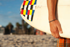 Closeup of a surfer holding a surfboard. Closeup shot of a surfer holding a surfboard at the beach Royalty Free Stock Images