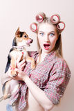 Closeup on surprised pinup sexy blond young beautiful woman holding a dog in her arms looking at camera portrait Royalty Free Stock Photography