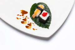 Sushi Nigiri and Hosomaki. Japanese Traditional Food. Closeup of sushi nigiri and hosomaki on a white plate over green leaf and white background. Creative Royalty Free Stock Photo