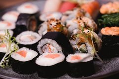 Closeup Sushi nigiri and rolls served on brown wooden table in plate. Healthy asian food. Macro photography Royalty Free Stock Images