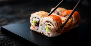 Closeup of sushi rolls with chopsticks Royalty Free Stock Image