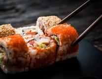 Closeup of sushi rolls with chopsticks Stock Photos