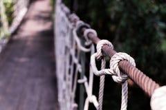 A closeup of suspension bridge rail detail. Closeup details of the rails are made of the ropes of the suspension bridge over the river, selective focus stock photography