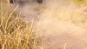 Closeup of SUV riding fast on the dirt road at countryside stock footage