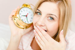 Closeup on sweet cute charming young woman blond girl with sleepy face and an alarm clock in hand Royalty Free Stock Photography