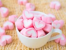 Closeup of sweet marshmallow in the shape of heart on wooden plate. And flower at background. Concept about love and relationship. Soft Style for Background Royalty Free Stock Image