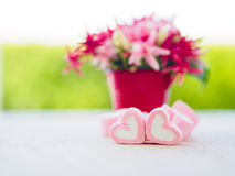 Closeup of sweet marshmallow in the shape of heart. On wooden plate and flower at background. Concept about love and relationship. Soft Style for Background Stock Photo