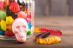 Closeup sweet skull wit sweet worms over wooden background Stock Photo