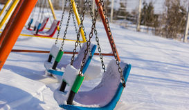 Closeup of swings in a children play area after snowfall Royalty Free Stock Photo