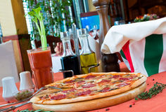 Closeup of a table with pizza and a cook hat Stock Photography