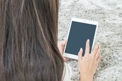 Closeup tablet computer on asian woman hand on blurred gray carpet floor textured background with copy space Stock Image