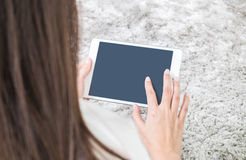 Closeup tablet computer on asian woman hand on blurred gray carpet floor textured background with copy space Royalty Free Stock Photography