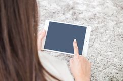Closeup tablet computer on woman hand and point by finger on blurred gray carpet floor textured background with copy space. Closeup tablet computer on woman hand Royalty Free Stock Photos